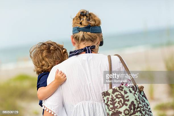 caucasian mother carrying baby son on beach - woman carrying tote bag stock photos and pictures