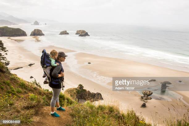 caucasian mother carrying daughter on beach - oregon coast stock pictures, royalty-free photos & images