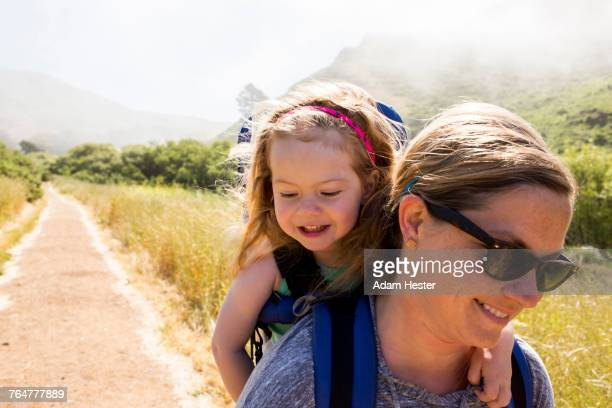 Caucasian mother carrying daughter while hiking