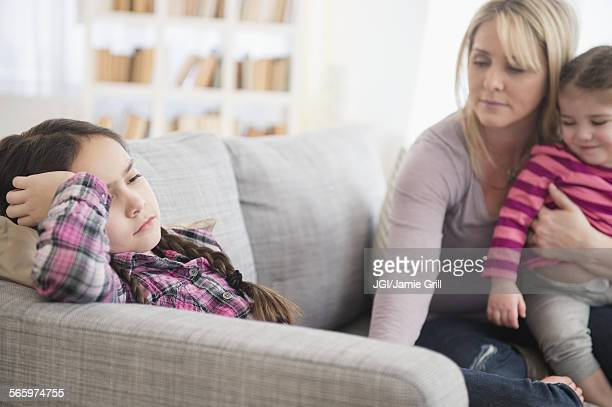 Caucasian mother comforting upset daughter on sofa