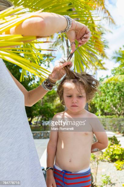 Caucasian mother cutting hair of son outdoors