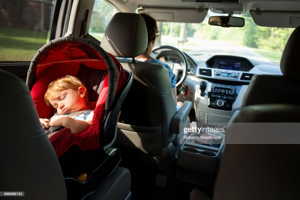 Caucasian mother driving car with baby son in car seat : Stock Photo
