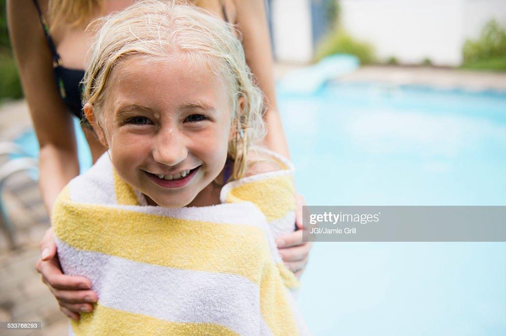 Caucasian mother drying daughter near swimming pool : Foto stock