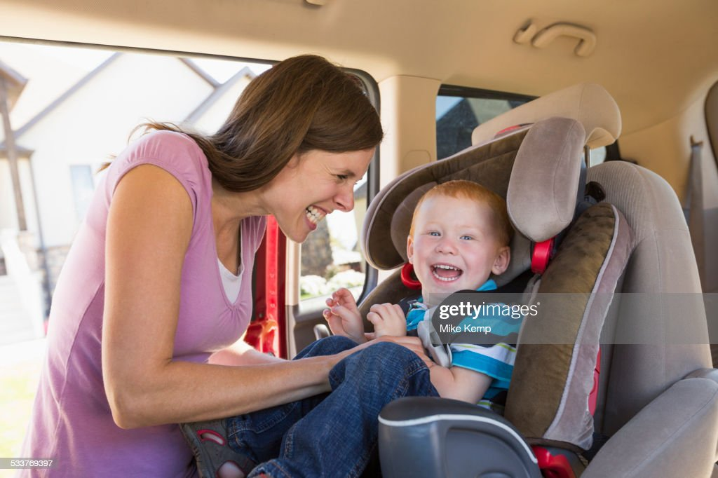 Caucasian mother fastening son into car seat : Foto stock