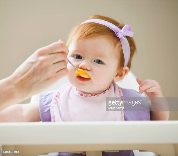 caucasian mother feeding baby girl - black ginger baby stock photos and pictures