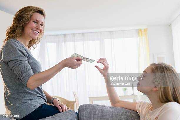 Caucasian mother giving daughter money