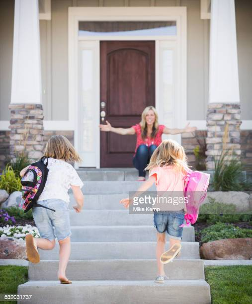 caucasian mother greeting daughters returning home from school - ankunft stock-fotos und bilder