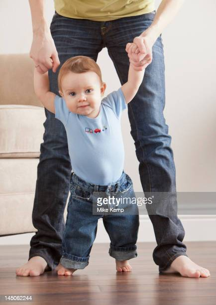 Caucasian mother helping son learn to walk