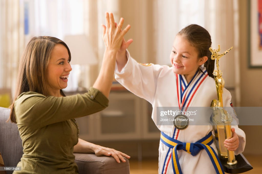 Caucasian mother high-fiving daughter for karate win : Stock Photo