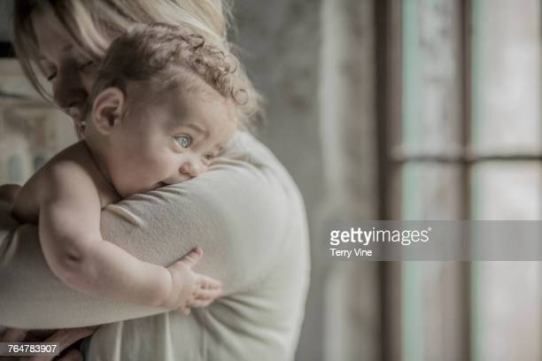caucasian mother holding baby boy near window - small faces stock pictures, royalty-free photos & images