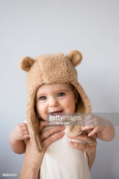 Caucasian mother holding baby daughter in fuzzy hat