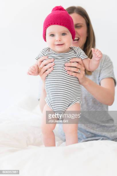 Caucasian mother holding baby daughter on bed