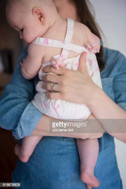 Caucasian mother holding baby daughter