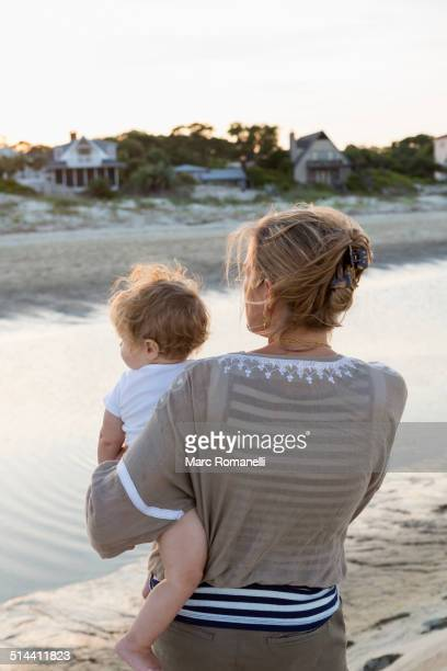 Caucasian mother holding baby on beach
