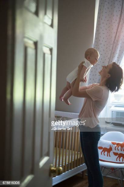 Caucasian mother holding baby son face to face in bedroom