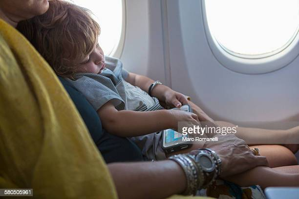 Caucasian mother holding baby son on airplane
