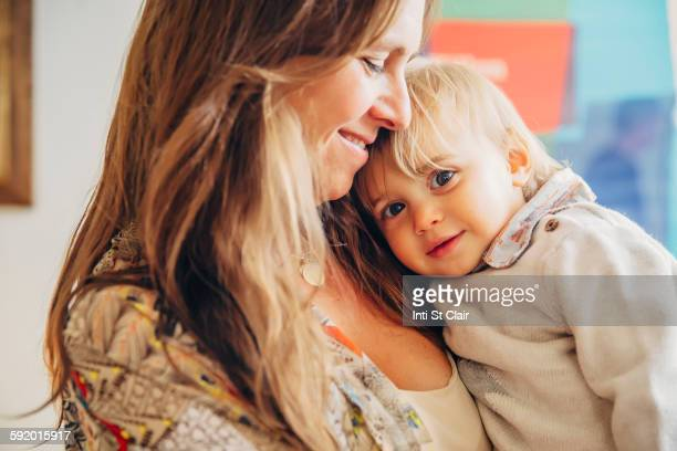 Caucasian mother holding baby son