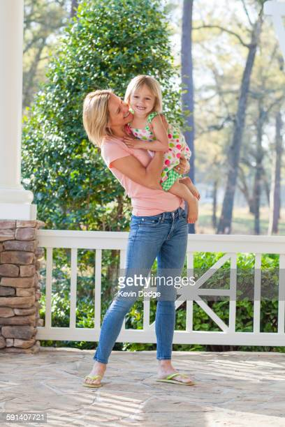 Caucasian mother holding daughter on patio
