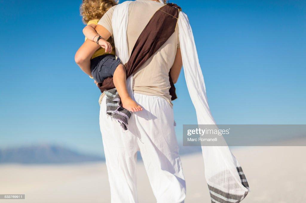 Caucasian mother holding son on sand dune : Foto stock