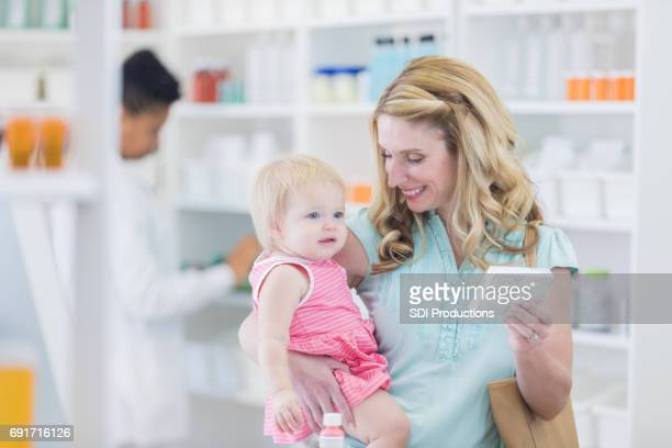 Caucasian mother holds her daughter in a pharmacy