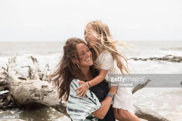 Caucasian mother hugging daughter near driftwood on beach