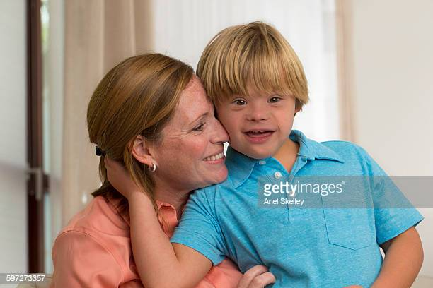 Caucasian mother hugging son with Down Syndrome