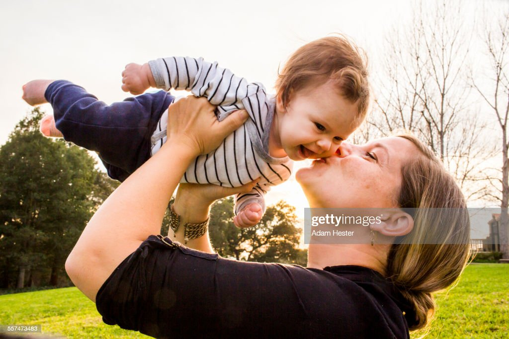 Caucasian mother kissing baby girl outdoors : Stock Photo