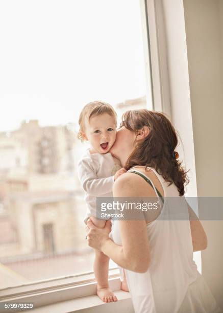 Caucasian mother kissing baby in window