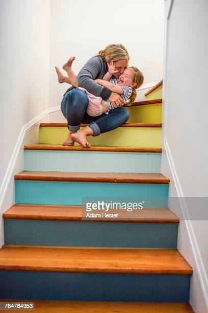 Caucasian mother kissing daughter on staircase