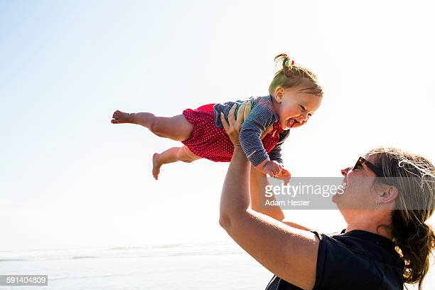 Caucasian mother lifting baby daughter on beach