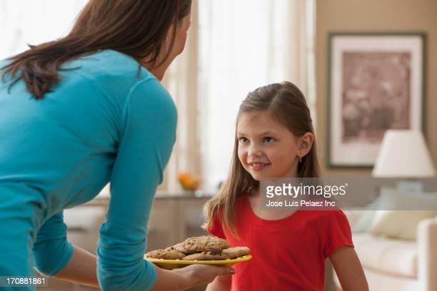Caucasian mother offering daughter cookies