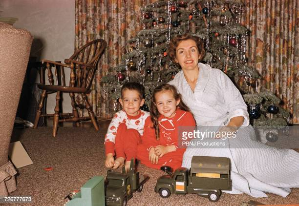 caucasian mother posing with son and daughter near christmas tree - archiefbeelden stockfoto's en -beelden