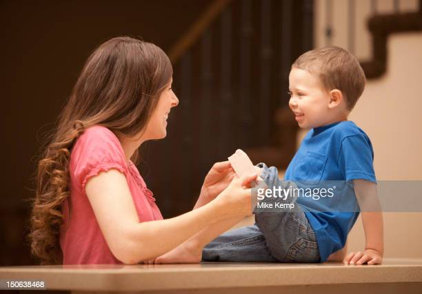 caucasian mother putting bandage on son's knee - healing wound stock pictures, royalty-free photos & images