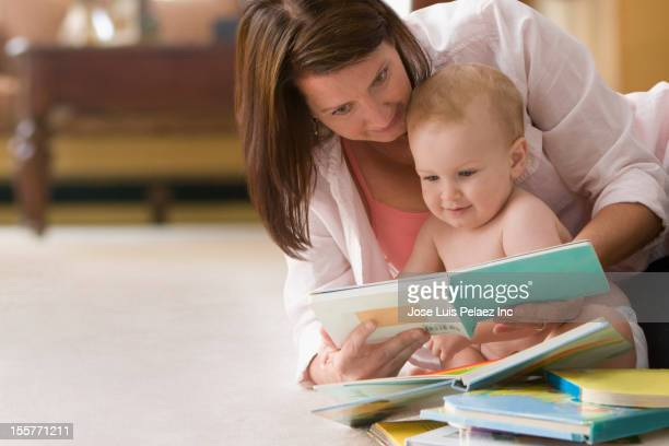 Caucasian mother reading book to baby boy