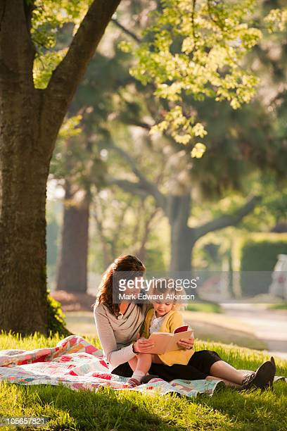 Caucasian mother reading story to daughter in park