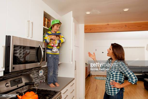 caucasian mother scolding son on counter top - mother scolding stock pictures, royalty-free photos & images