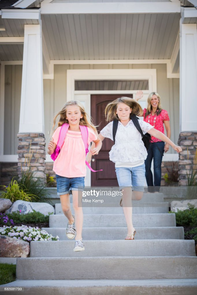 Caucasian mother sending running sisters to school : Stock Photo