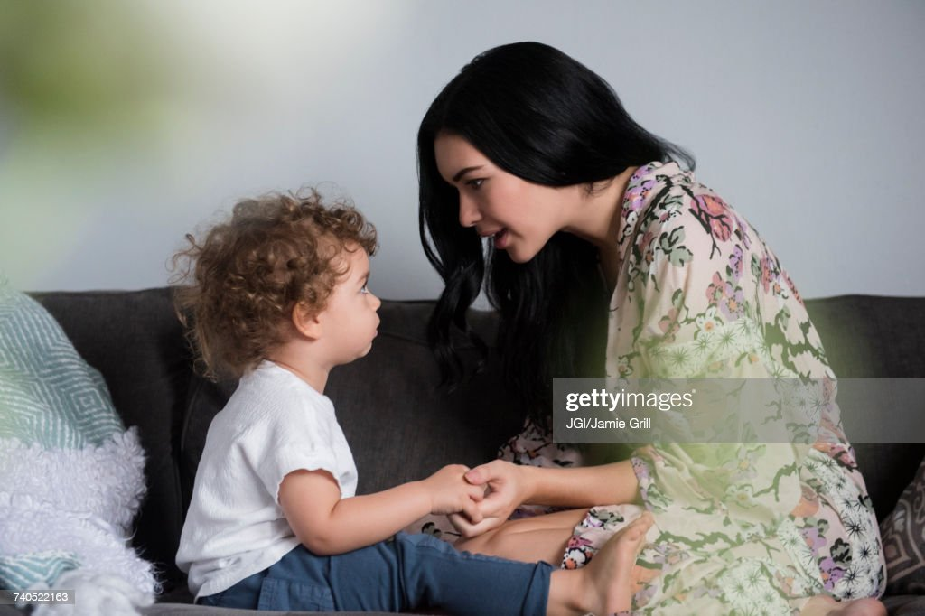 Caucasian mother sitting on sofa holding hands and talking with son : Stock Photo