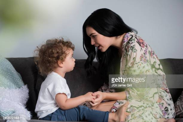caucasian mother sitting on sofa holding hands and talking with son - mother scolding stock pictures, royalty-free photos & images