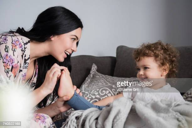 Caucasian mother sitting on sofa playing with toes of son