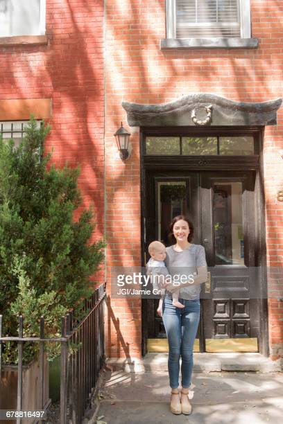 Caucasian mother standing near doorway holding baby son