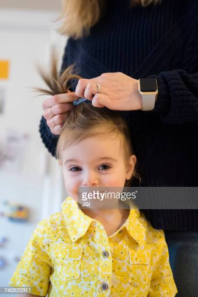 Caucasian mother styling hair of baby daughter