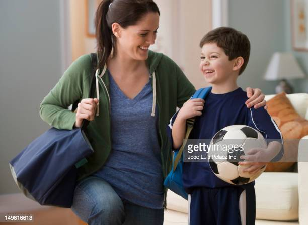Caucasian mother talking to son holding soccer ball