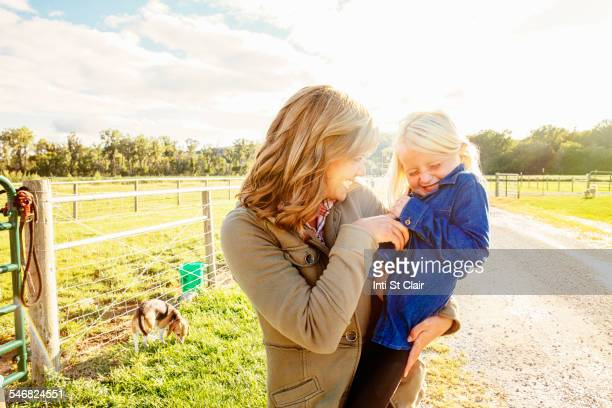 caucasian mother tickling daughter on rural road - nebraska stock pictures, royalty-free photos & images