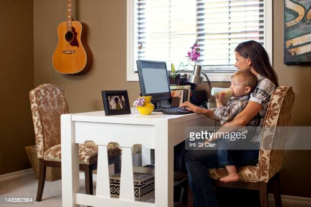 Caucasian mother using computer with son on lap