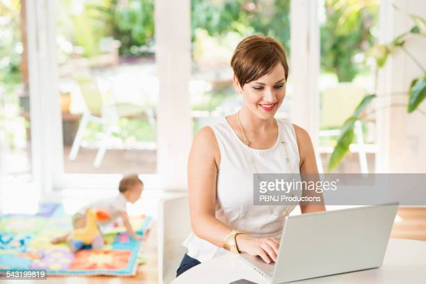 Caucasian mother using laptop at counter