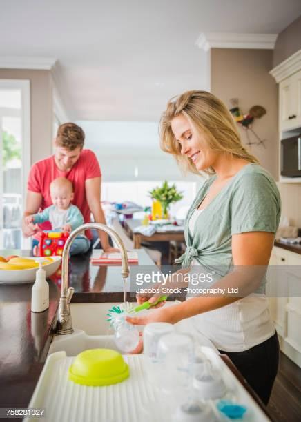 caucasian mother washing baby bottle - 洗う ストックフォトと画像