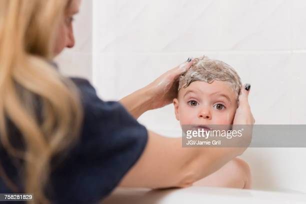 Caucasian mother washing hair of girl in bathtub