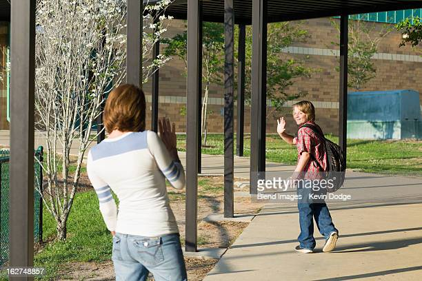 caucasian mother waving to son - waving gesture stock photos and pictures