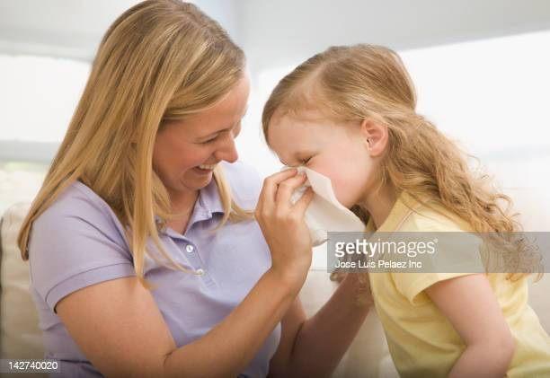 Caucasian mother wiping daughter's nose